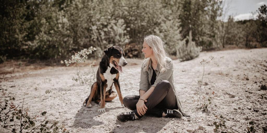 Einzelcoaching Melanie mit Hund im Sand und schauen sich an